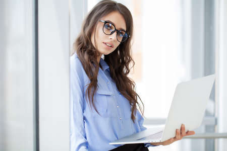 Charming businesswoman near window working on laptop in office Archivio Fotografico - 154785552