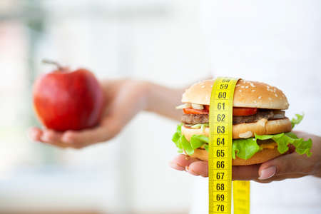 Diet concept, woman holding a choice of harmful hamburger and fresh apple