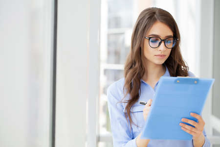 Young beautiful business woman with clipboard in the office. Archivio Fotografico - 154786805