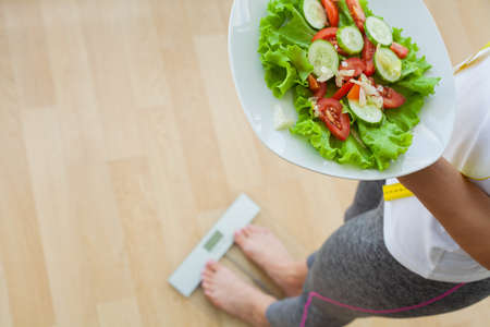 Diet concept, woman holding fresh diet salad measure her weight
