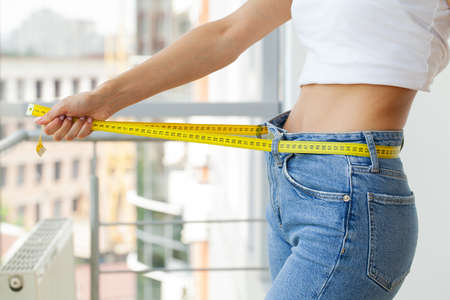 Slender woman in jeans and a white T-shirt measures her waist