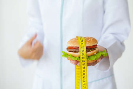Diet concept, doctor holding harmful fat burger with yellow measuring tape Archivio Fotografico - 154785781