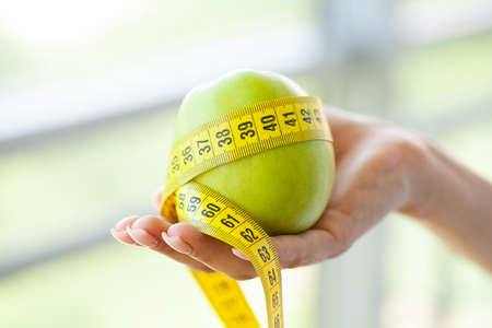 Diet concept, woman holding an apple with a measure tape around it Imagens