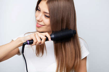 Woman With Beautiful Long Straight Hair Using Hair Straightener