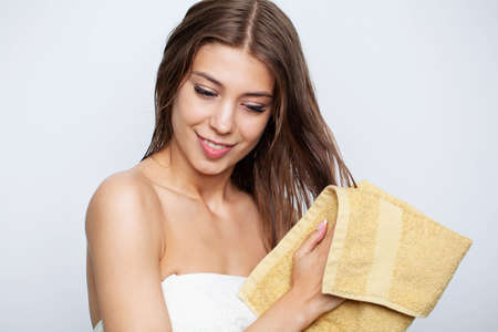 Beautiful young woman wipes her hairs with a towel. Imagens