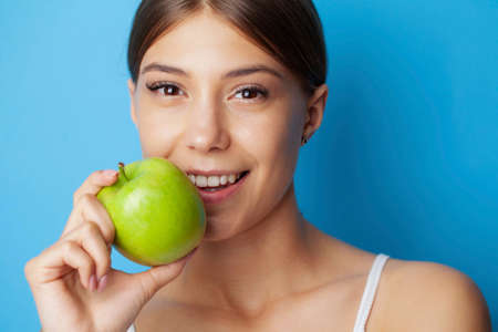 Portrait of a cheerful young woman with perfect smile eating green apple