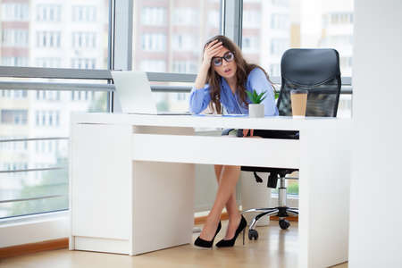 Young office worker sitting at desk holding head because of pain in office