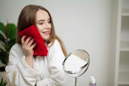 Cute woman cleaning facial skin with towel after washing face portrait Archivio Fotografico