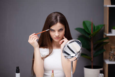 Young woman applying makeup on face at home Archivio Fotografico