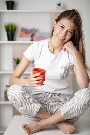 Young beautiful woman wearing pajama drinking cup of coffee