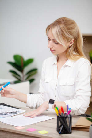 Business woman sitting at desk in office and examines documents