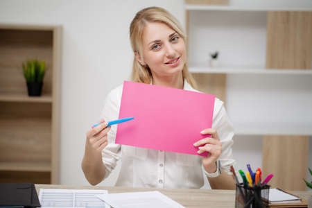 Business woman sitting at desk holding empty paper Archivio Fotografico