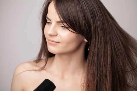 Beautiful long haired woman drying hair in bathroom 版權商用圖片