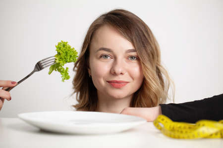 Portrait of happy smiling young beautiful woman eating broccoli Archivio Fotografico