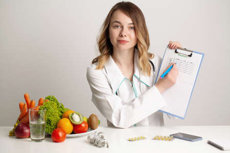 Young nutritionist doctor writing diet plan, healthy eating