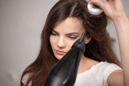 Beautiful long haired woman drying hair in bathroom Stockfoto