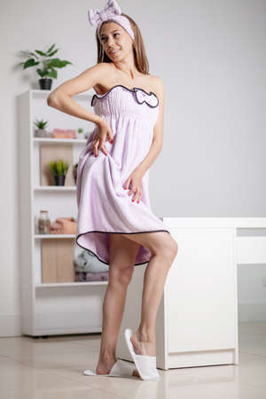 Pretty woman trying on a towel dress and a makeup bandage Archivio Fotografico