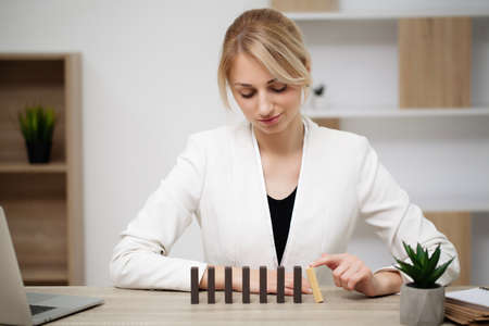 Young business woman in the office makes wooden cubes Archivio Fotografico