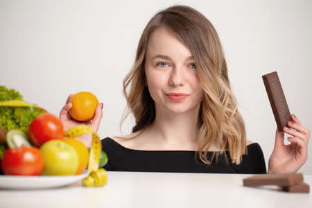 Young woman makes a choice between healthy and unhealthy food