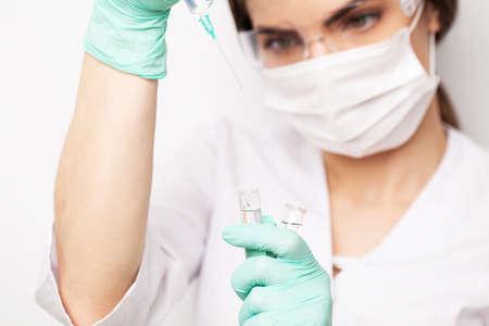 Hands of the doctors filling a syringe