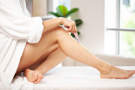 Skin care and health, fit woman shaving her legs with razor.