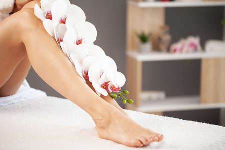 Long legs of a woman with a fresh manicure and orchid flowers Archivio Fotografico