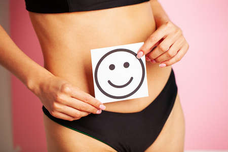 Woman holding paper with smile mark over her stomach. Health hygiene sexual education concept.