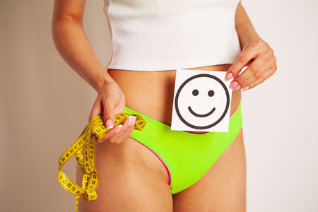 Close up of a woman with a slender figure shows the result holding a card near her belly with a smile and a yellow tape measure.