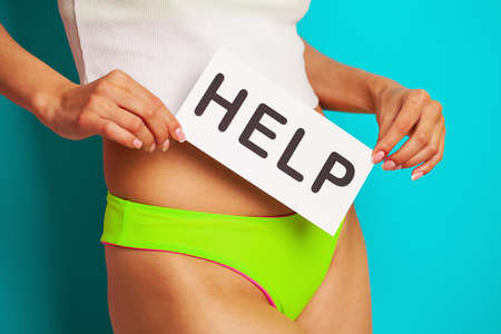 Womens health. Female body holding a help card symbol near the stomach.