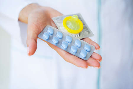 Close up of female doctor holding pill for men health