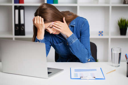 Woman working at office desk in front of laptop suffering from chronic daily headaches.