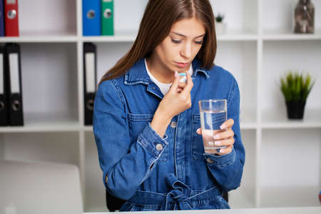 Beautiful young woman taking pill at office