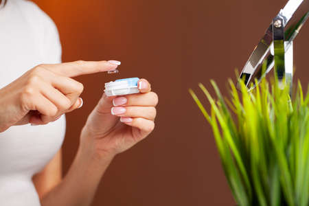 Young woman holding contact lens on finger. Banque d'images