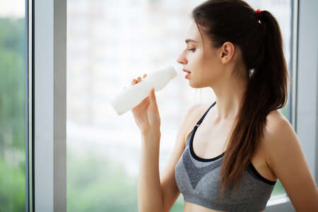 Young beautiful woman drinking from plastic bottle of yogurt