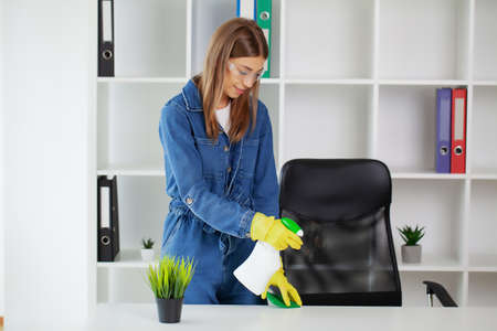 Pretty woman in uniform with supplies cleaning in office