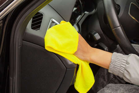 Hand with yellow microfiber cloth polishing car