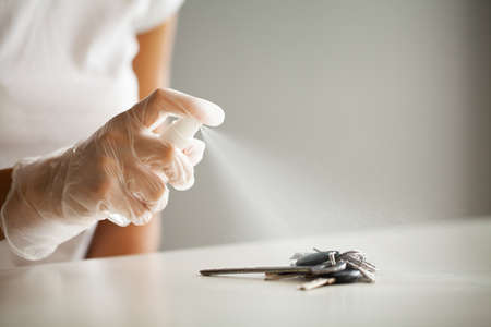 Woman disinfecting keys with disinfectant on the table Banque d'images - 158417157