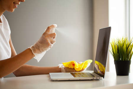 Woman disinfect laptop and smartphone by wet wipes and antiseptic