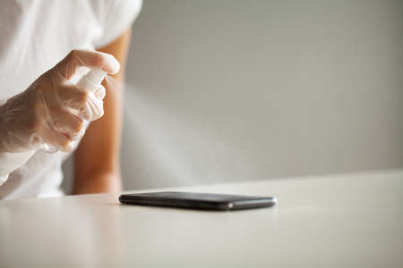 Close up woman disinfecting phone with antiseptic Banque d'images - 158417174