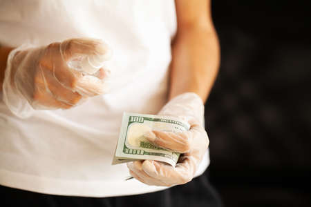 Close up woman disinfect money with antiseptic. Banque d'images