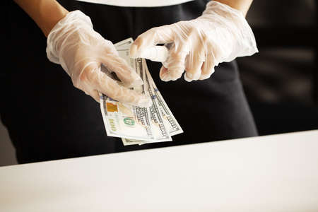 Close up woman disinfect money with antiseptic. Zdjęcie Seryjne