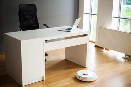Robot vacuum cleaner performs automatic cleaning of the apartment at a certain time. Smart home.