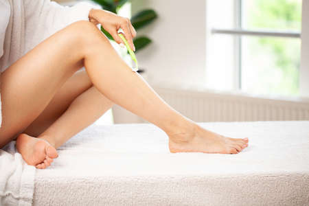 Female legs and shaving razor on white background Banque d'images