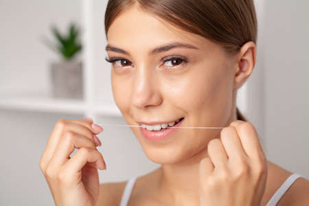 Portrait of beautiful woman cleaning teeth with dental floss Stock Photo