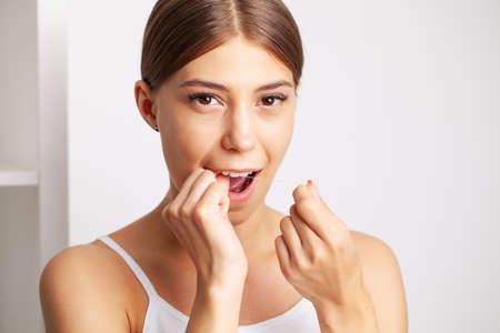 Cheerful brunette woman using dental floss in bathroom Reklamní fotografie