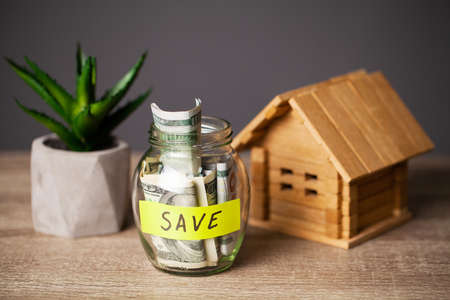 Dollar bills in glass jar and text save on wooden table Reklamní fotografie