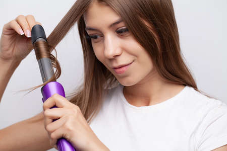 Young woman with luxurious hair straightens it with a curling iron Banque d'images