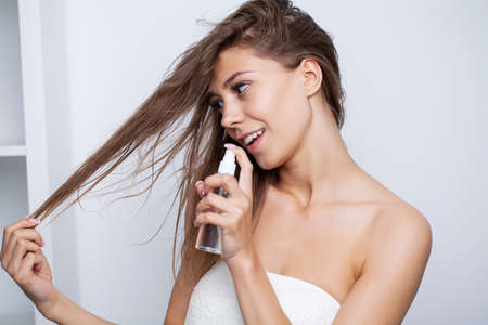 Woman with beautiful hair, applies vitamins for hair growth