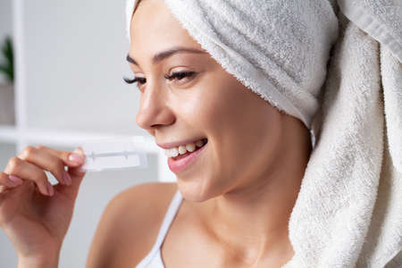 Teeth whitening, beautiful smiling woman holding a whitening strip. Banque d'images