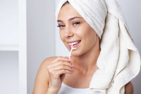 Portrait of beautiful woman cleaning teeth with dental floss Banque d'images